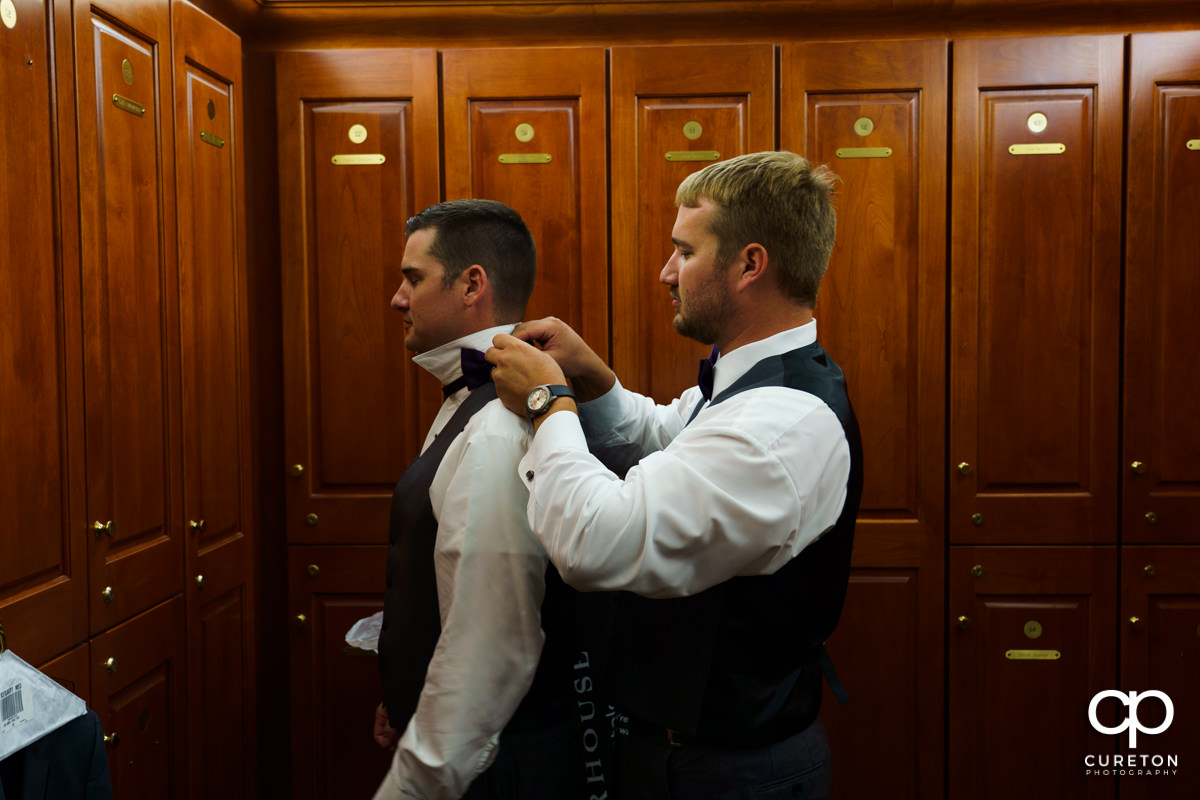 Groom's brother helping him with his tie.
