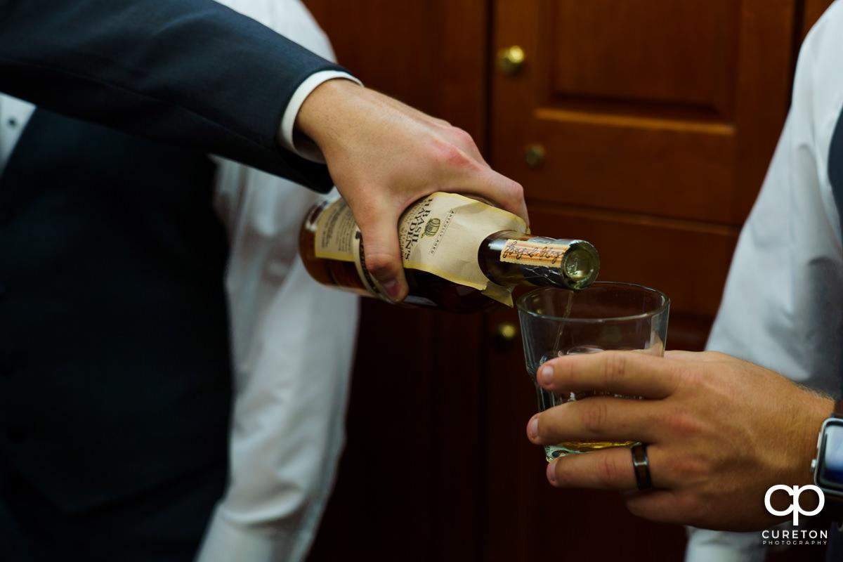 Groom pouring bourbon.