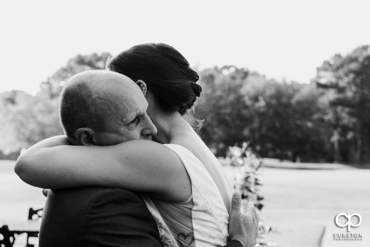 Bride hugging her dad after they have an emotional first look before the wedding ceremony.