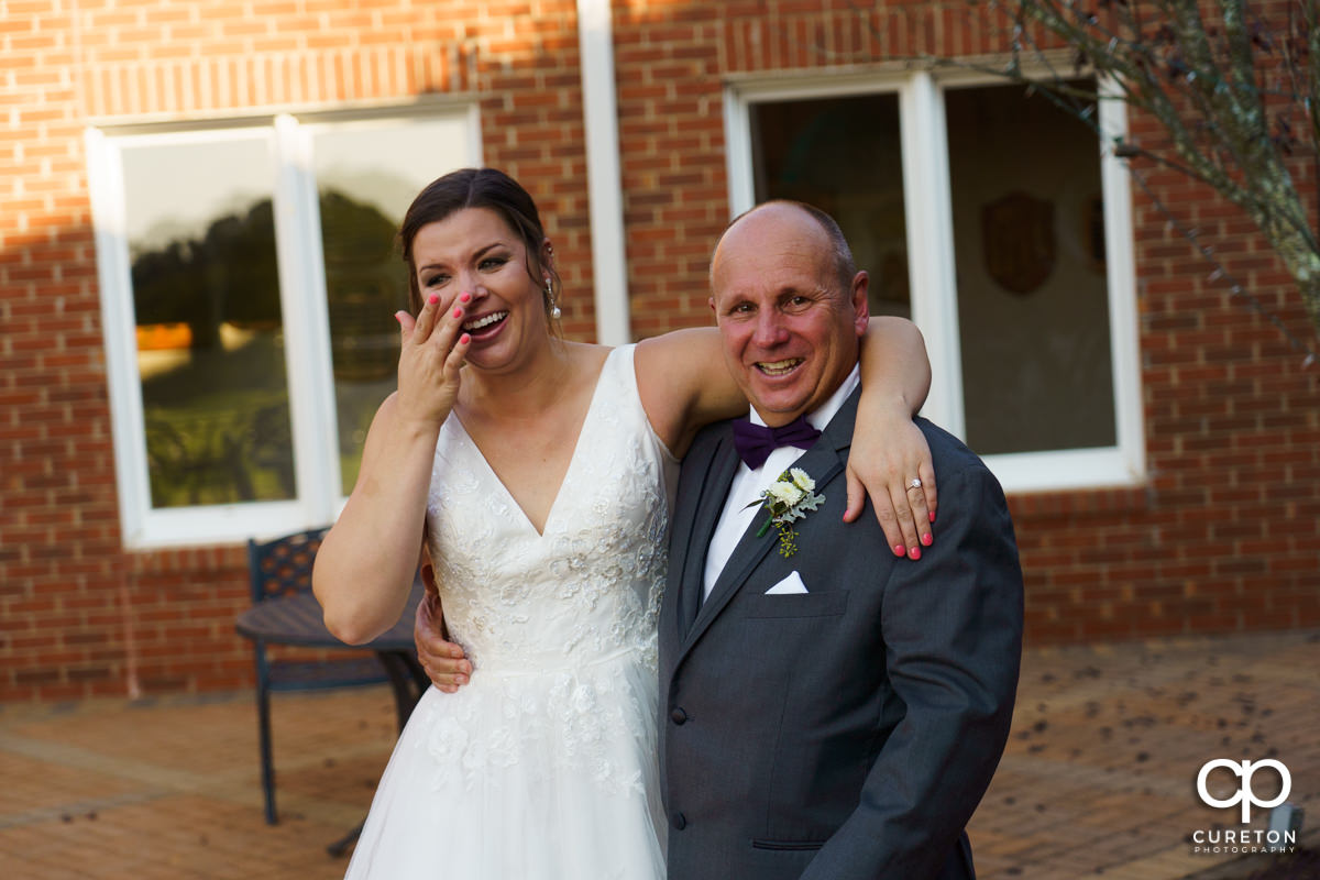 Bride and her dad wiping away tears after a first look.