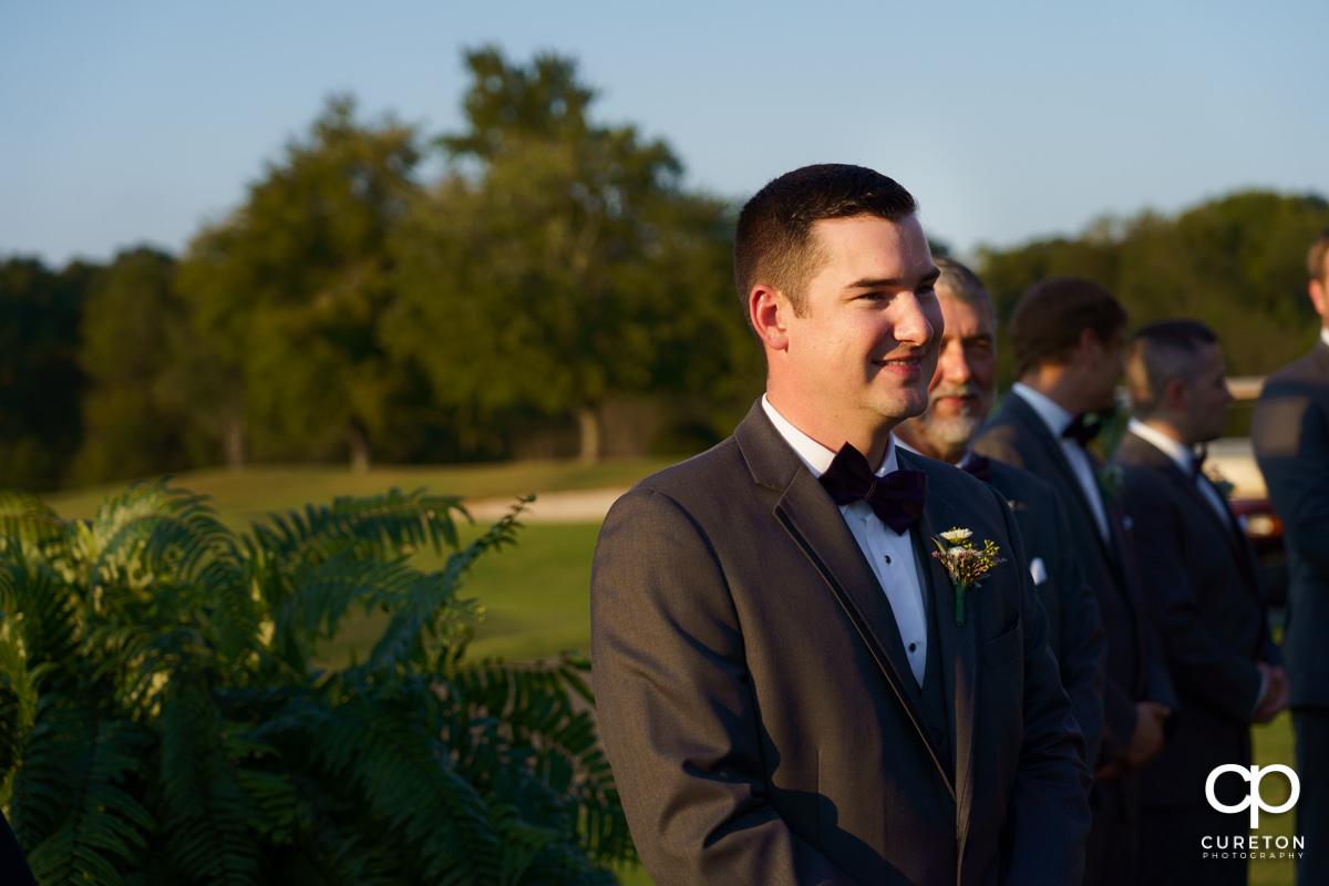 Groom smiling as his bride is walking down the aisle.