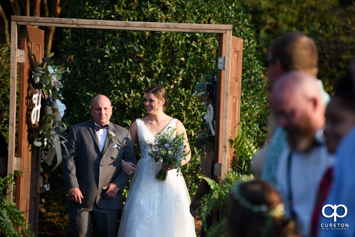 Bride and her father walking down the aisle through the wooden doors at the ceremony.