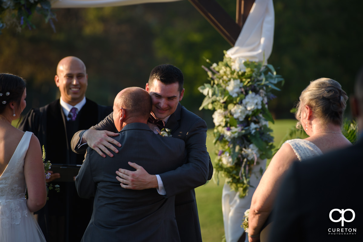 Groom hugging the bride's father at the ceremony.