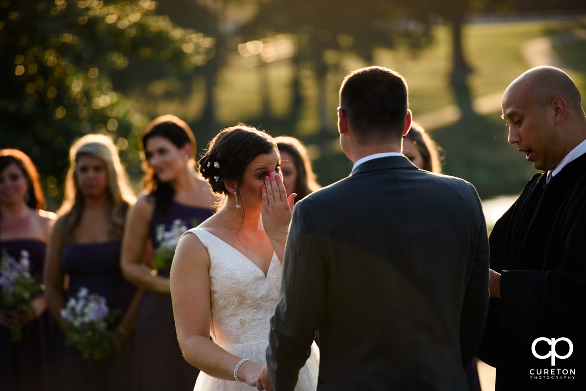 Bride wiping a tear from her eye during her wedding ceremony at Holly Tree Country Club.