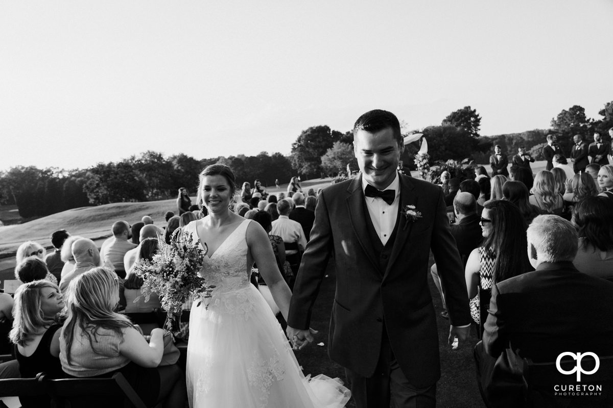 Bride and groom walking back down the aisle at he end of the wedding ceremony.