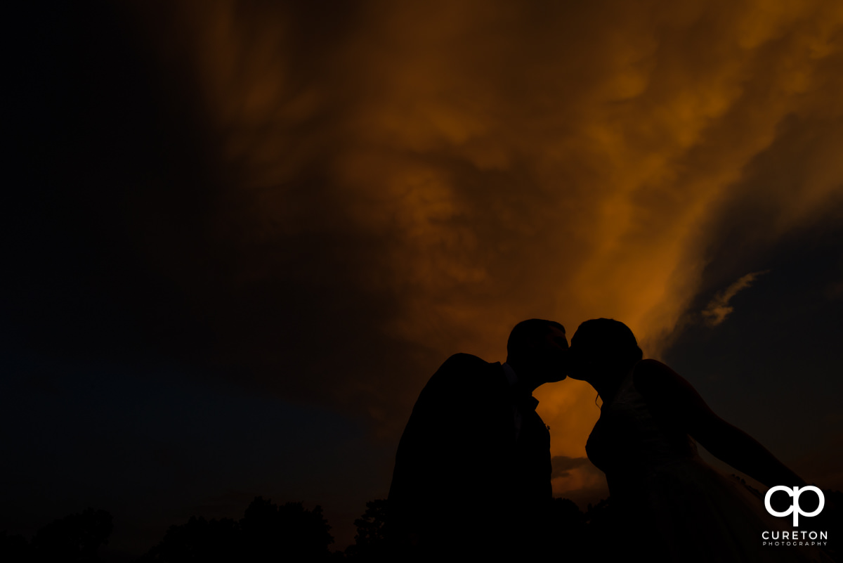 Bride and groom kissing silhouette at sunset.