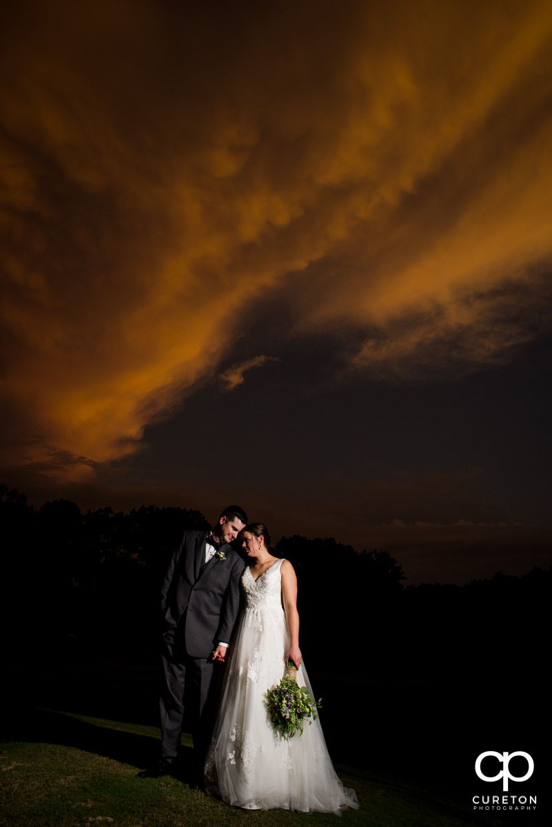 Newlyweds leaning into each other at sunset after their Holly Tree Country Club wedding ceremony.