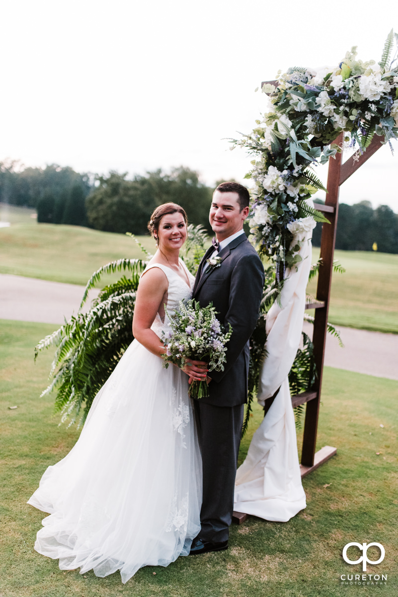 Groom and bride standing near a floral arch at their golf course wedding.