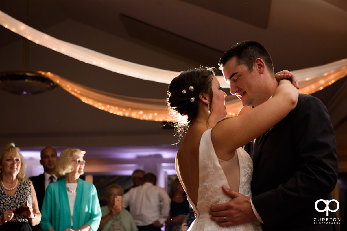 Groom smiling at his bride during the first dance at their Holly Tree Country Club wedding reception.