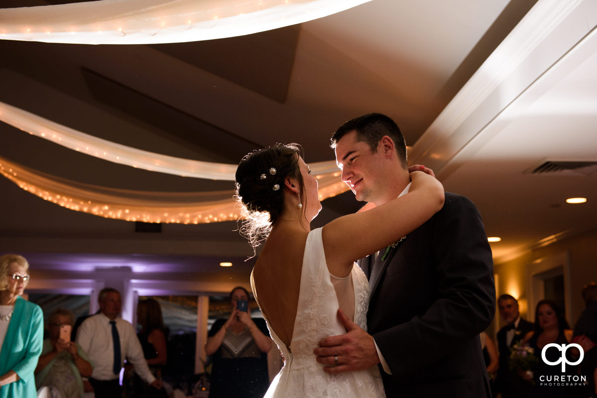 Groom and bride smiling at each other during their first dance.