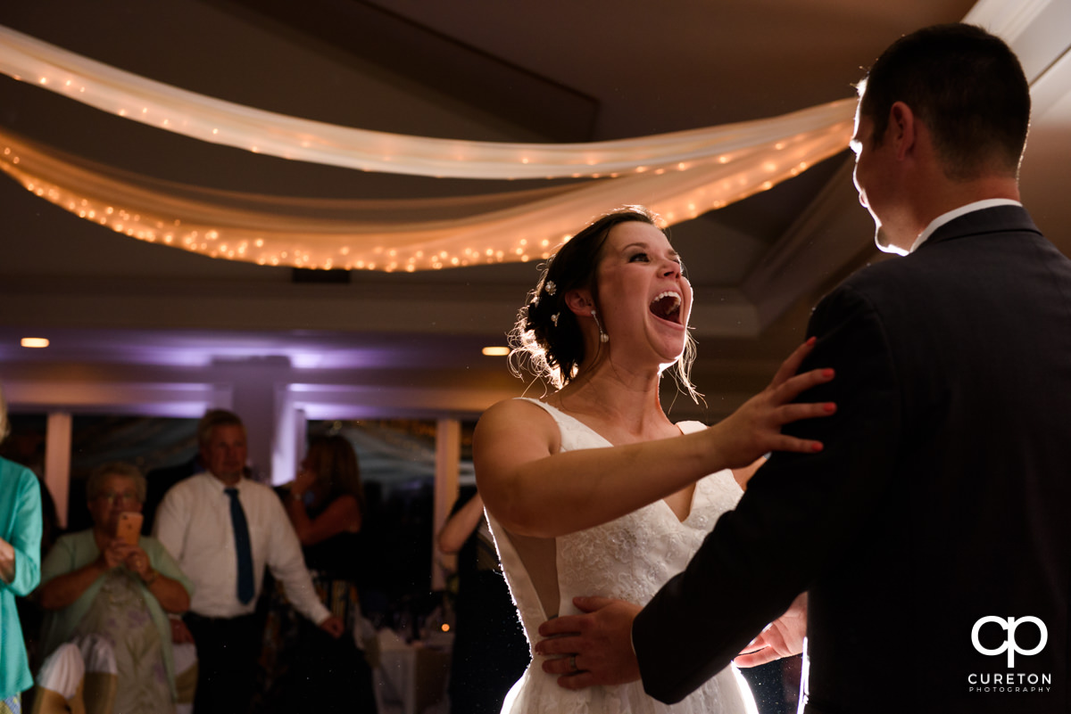 Bride smiling and laughing at the groom during their first dance at their Holly Tree Country Club wedding reception.