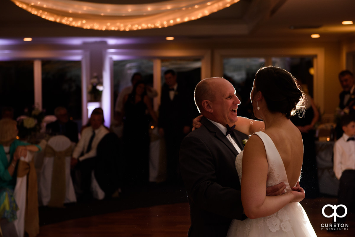 Bride's father smiling at his daughter during their dance at the wedding reception.