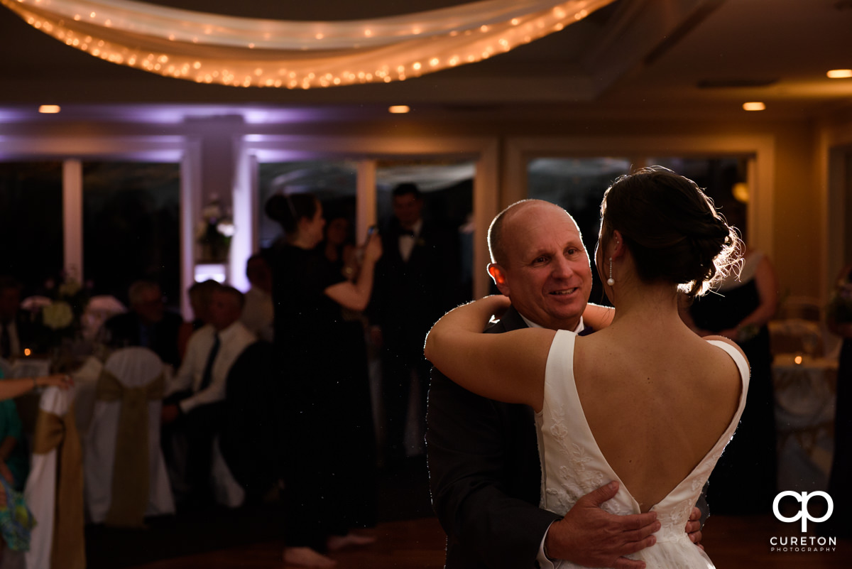 Bride's father dancing with his daughter during her wedding reception.