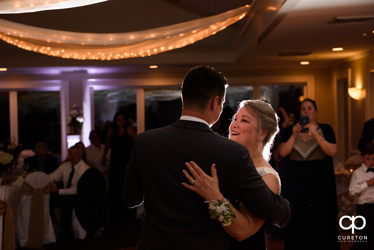 Groom's mother dancing with her son at the wedding reception.