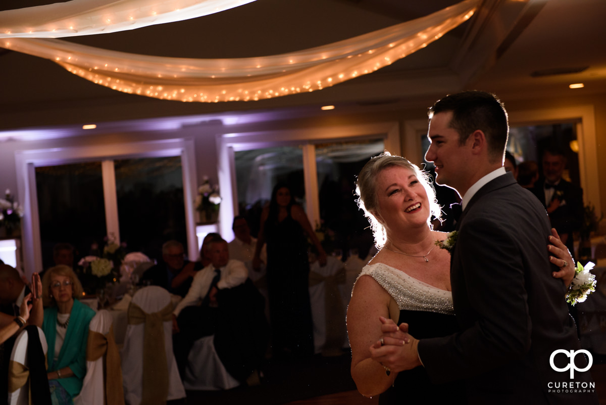 Groom's mother smiling at her son as they share a dance at the wedding reception.