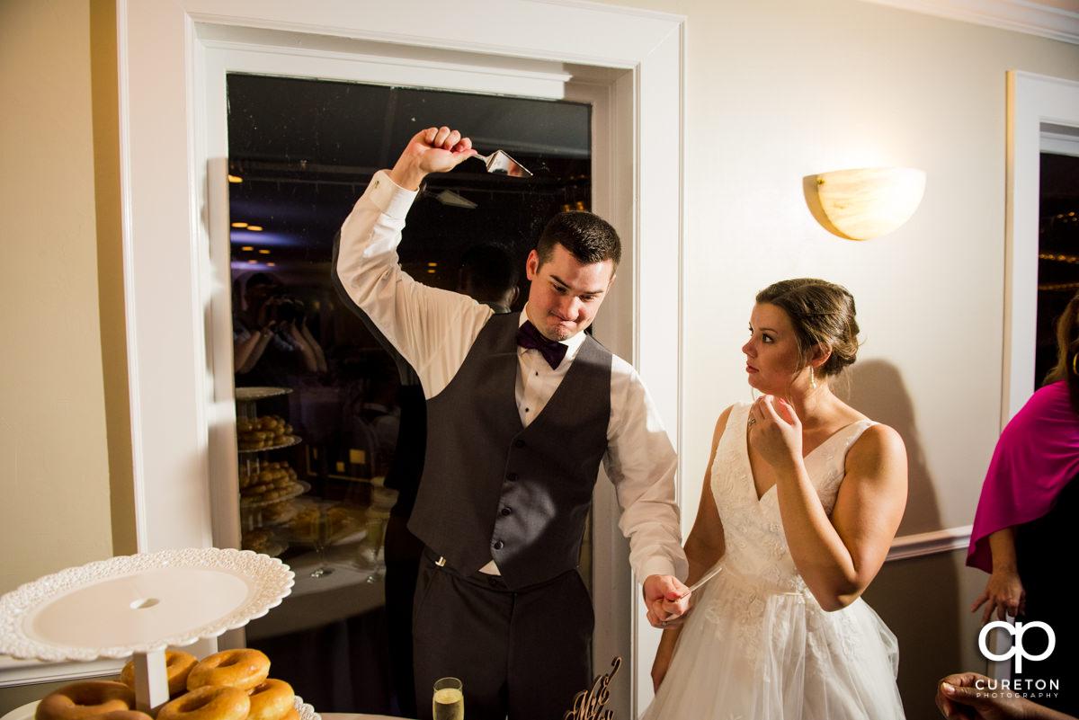 Groom slicing the wedding cake.