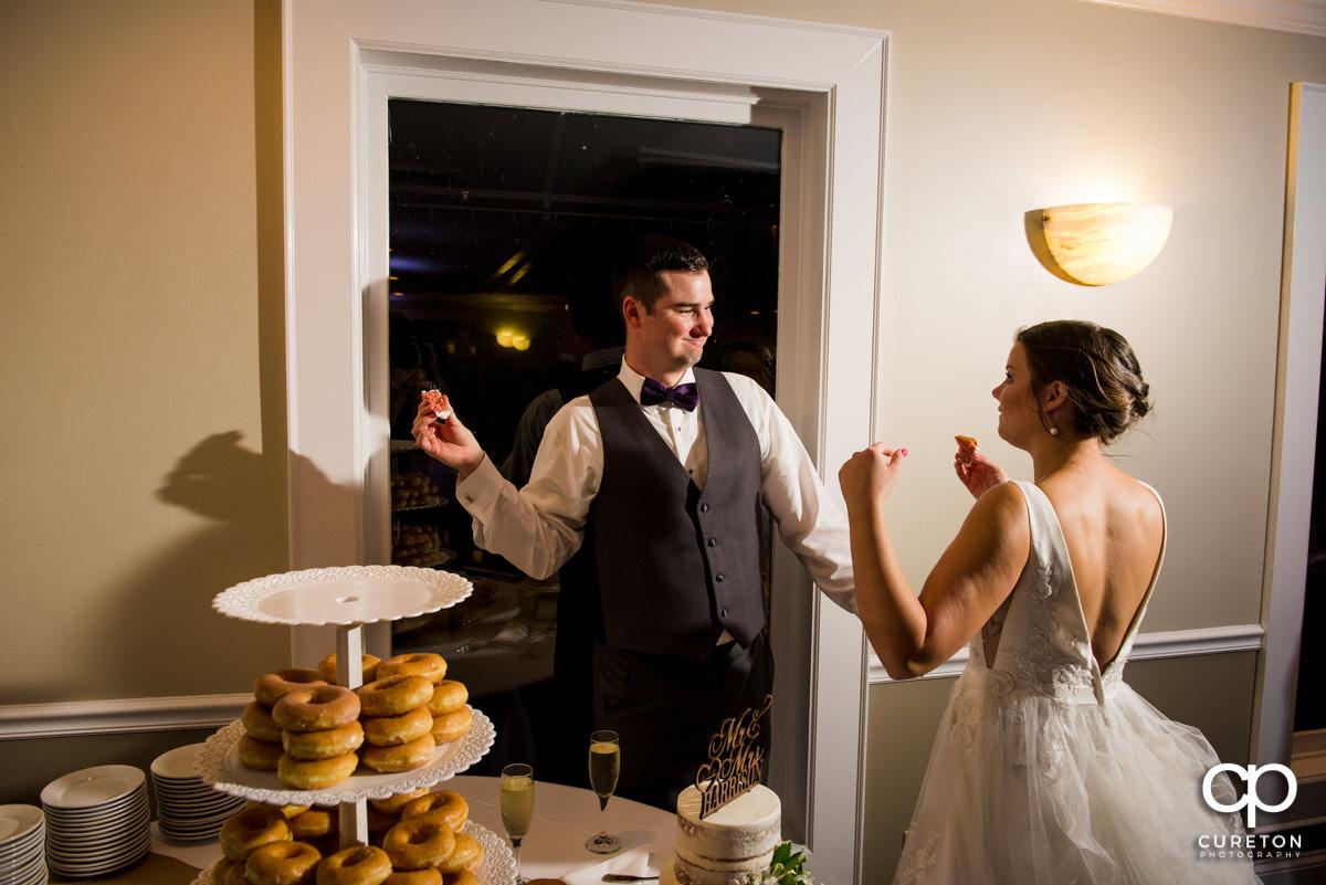 Bride an groom feeding each other wedding cake.