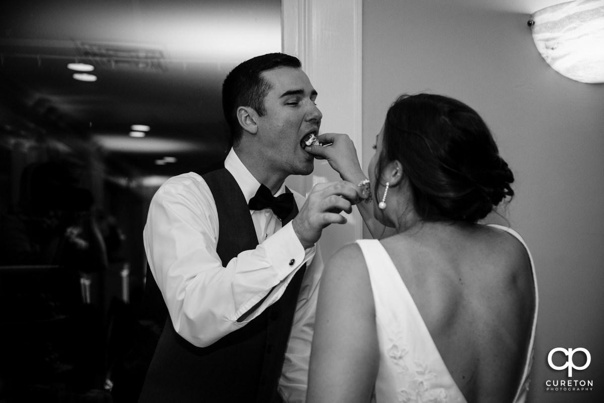 Bride feeding the groom cake.