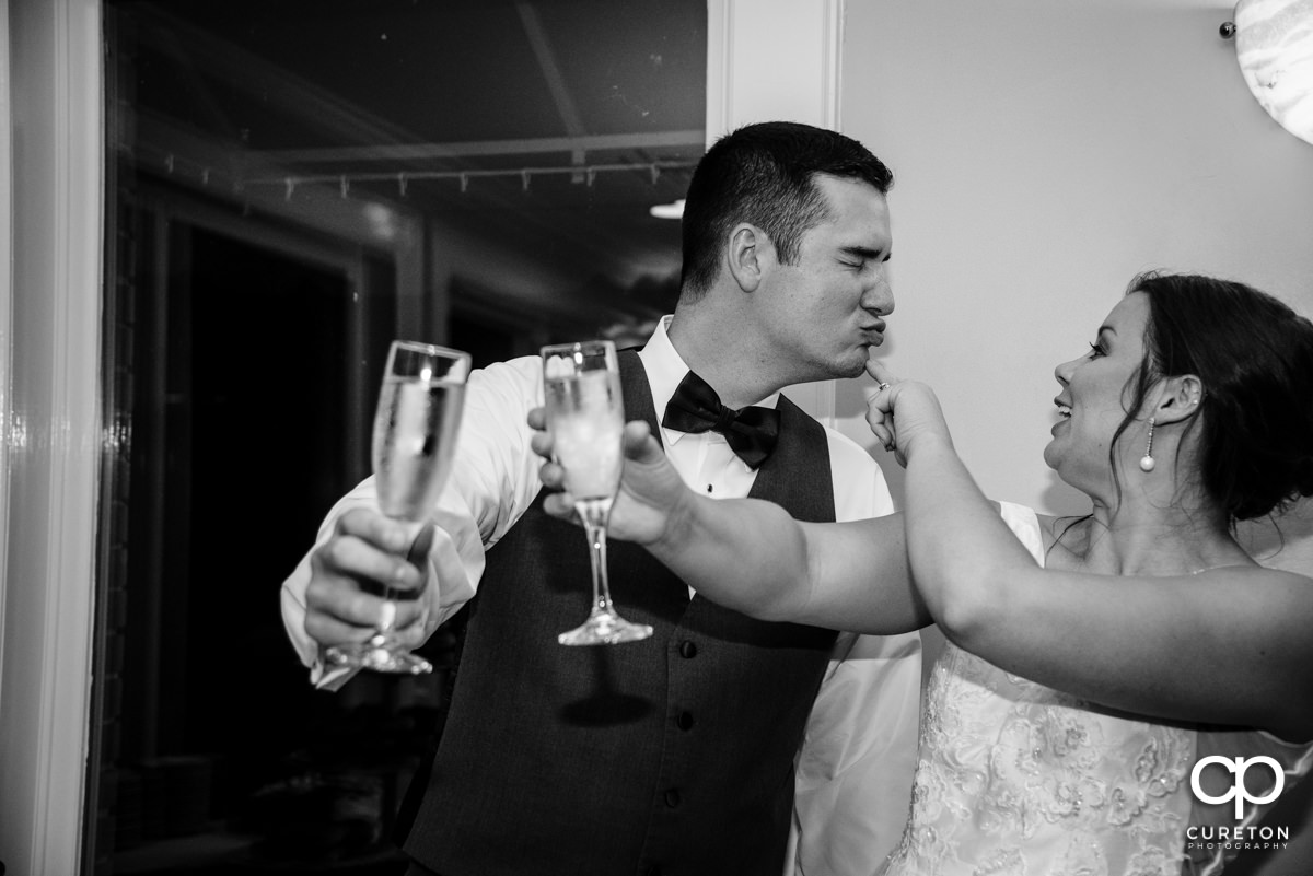 Bride and groom feeding each other wedding cake.