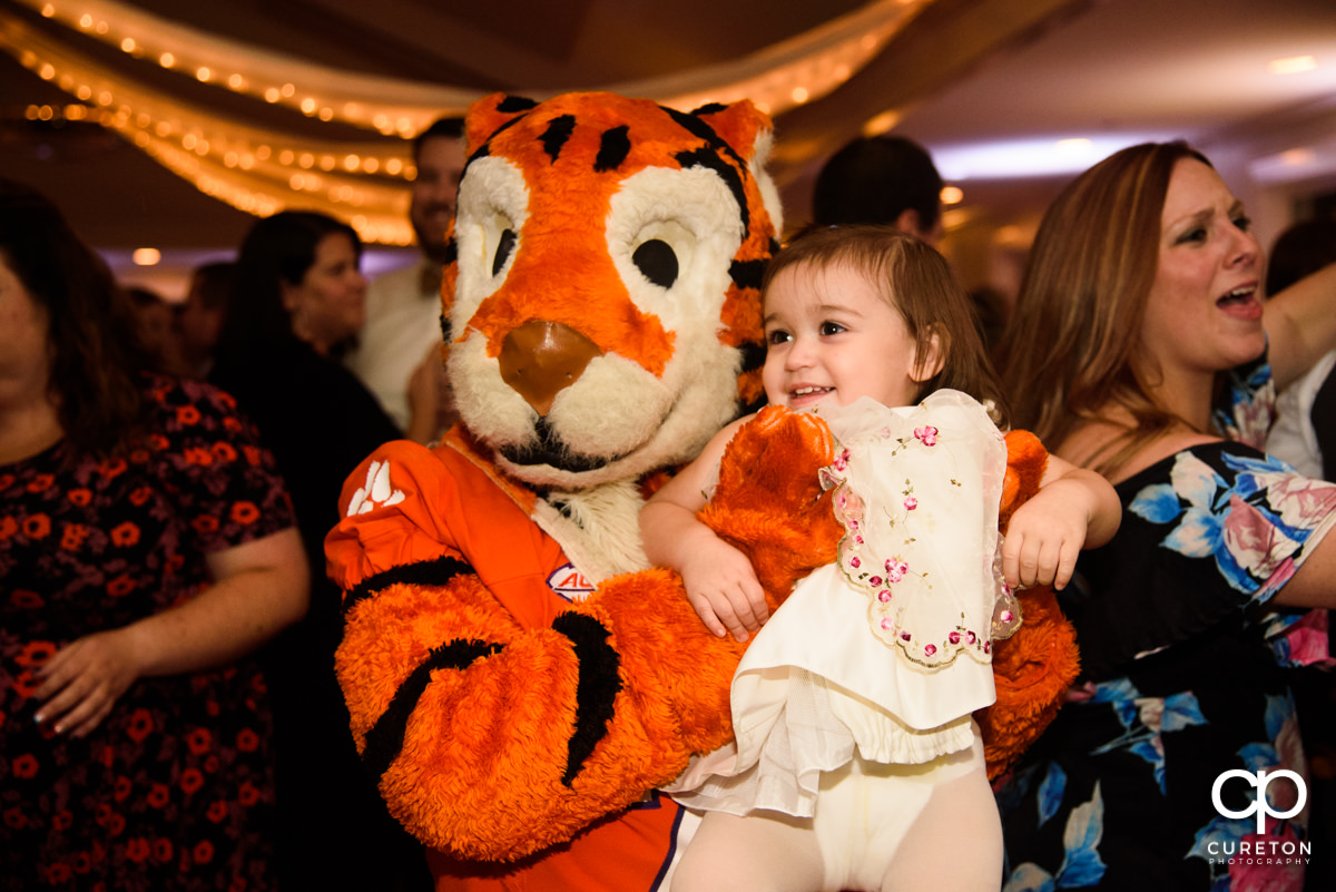 Clemson Tiger holding a baby at the reception.