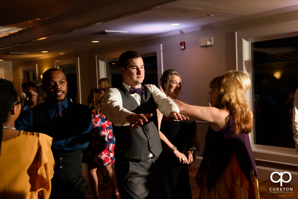 Wedding guests dancing to the sounds of the Party Machine dj at a wedding reception at Holly Tree Country Club.