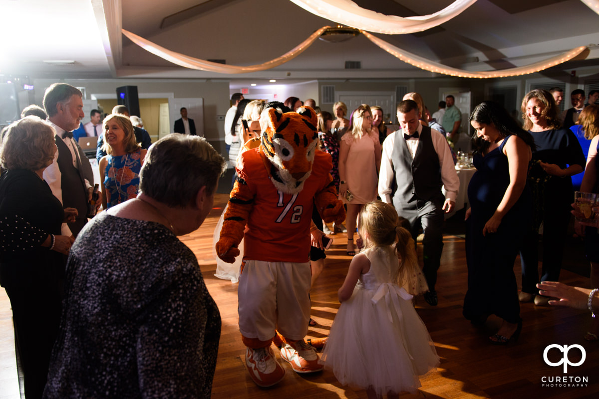 Clemson Tiger dancing with a child at a wedding reception.