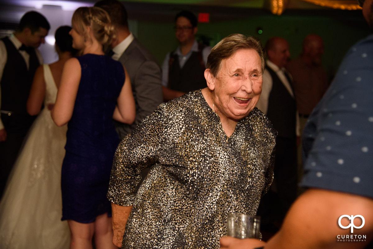 Grandma smiling and dancing at the reception.