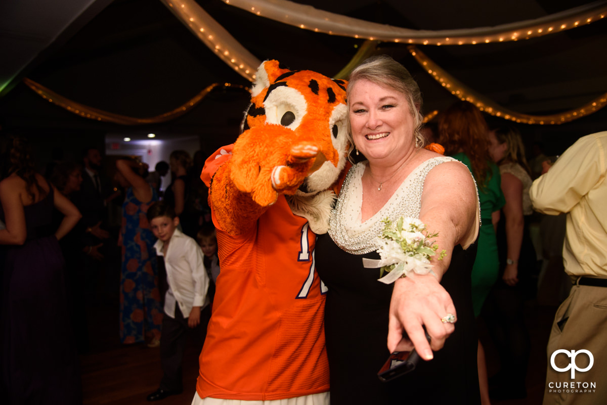Groom's mother posing with the Clemson Tiger Cub at the wedding reception.