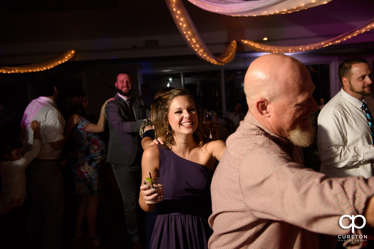 Wedding guests dancing a train at the reception.