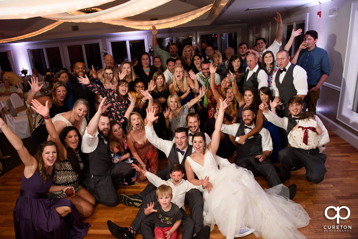 All the wedding guests posing for a photo on the dance floor.