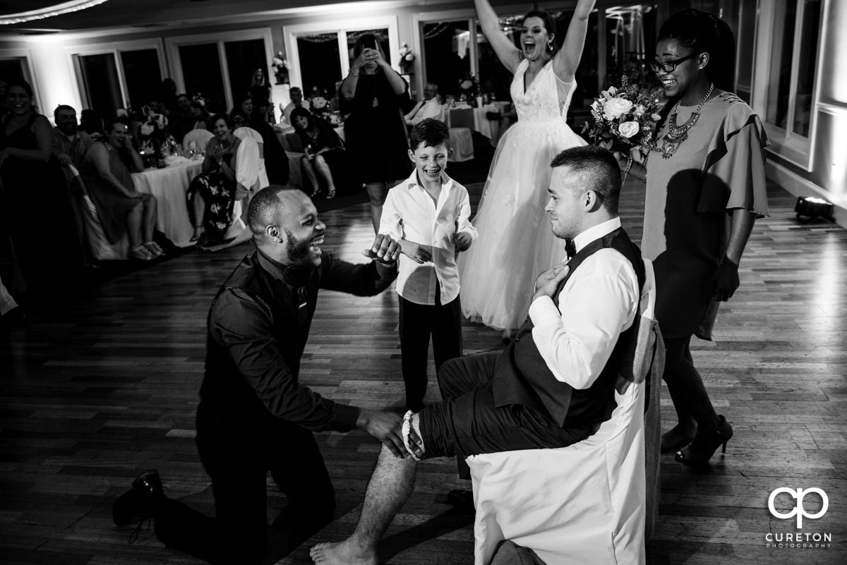The person who caught the garter tricked into putting it onto a groomsmen,
