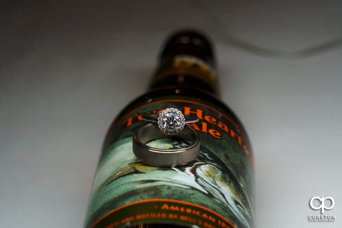 Wedding rings on a bottle of beer closeup.