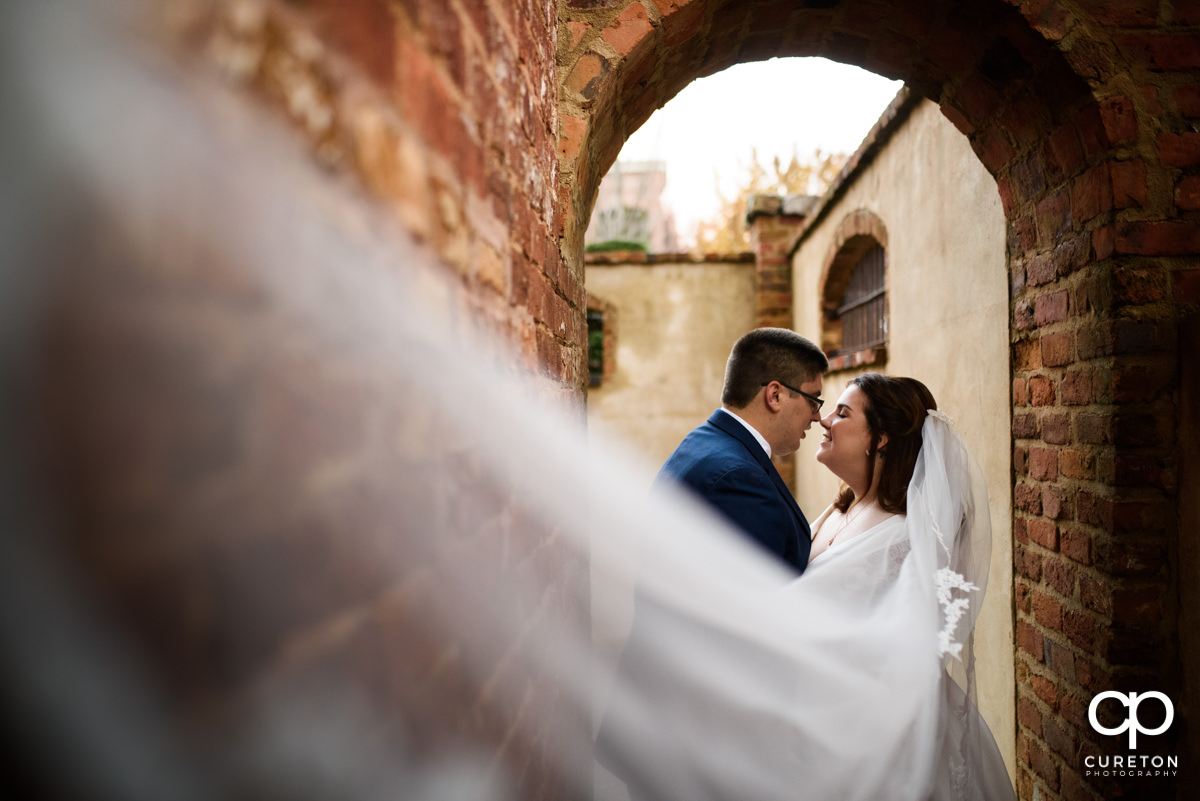 Bride and groom dancing nose to nose as her veil blows towards the camera during their fall wedding at the Old Cigar Warehouse in downtown Greenville,SC.