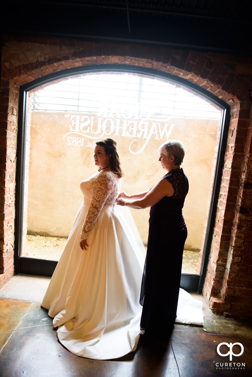 Bride's mother helping her into her dress in front of a window at The Old Cigar Warehouse.
