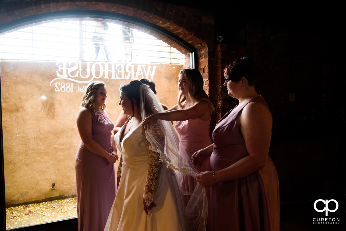 Bridesmaids helping the bride into her wedding dress before the ceremony at The Old Cigar Warehouse.