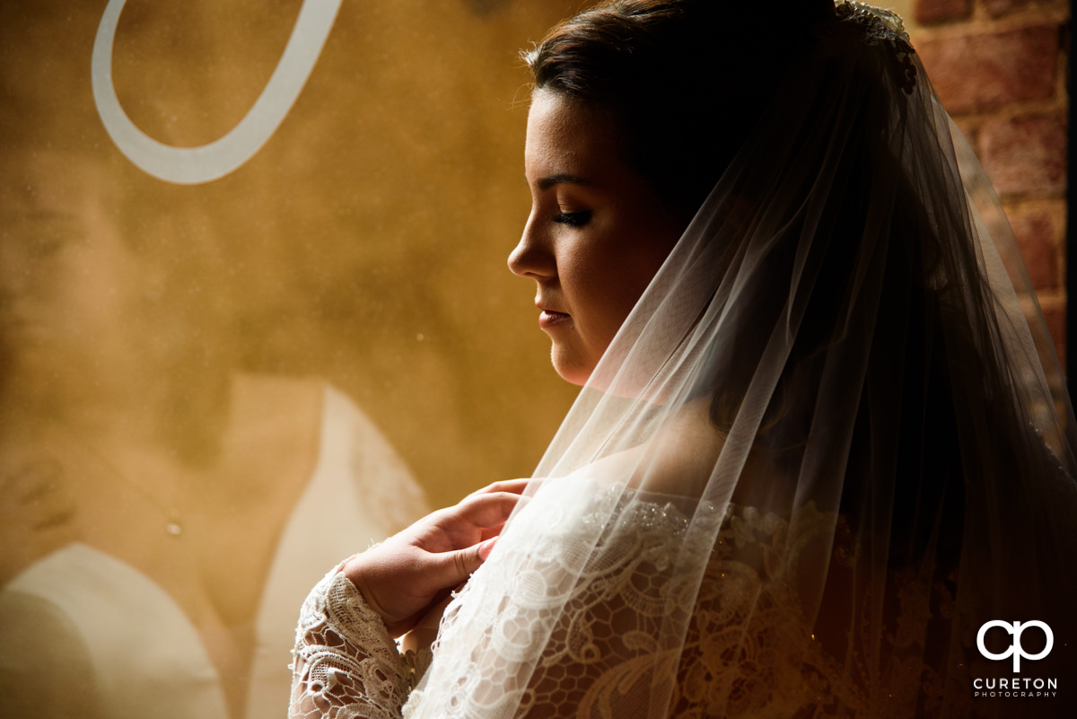 Bride looking at her veil in front of a huge bay window at The Old Cigar Warehouse in downtown Greenville,SC.