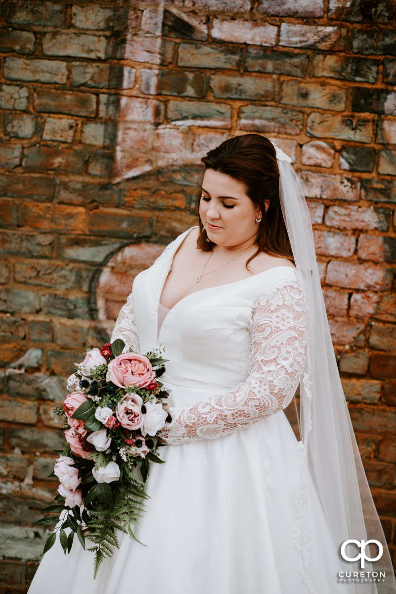 Bride holding her flowers out on the deck at Old Cigar Warehouse.