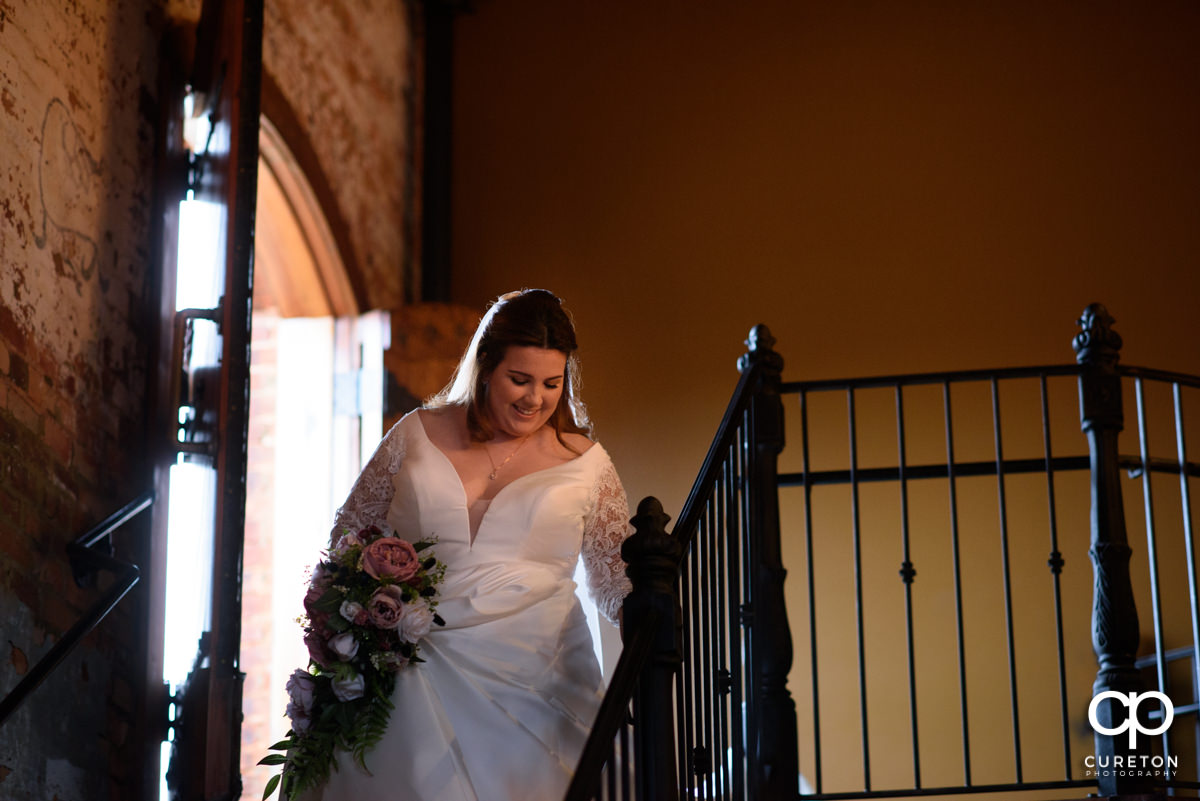 Bride making a grand entrance down the staircase into the wedding ceremony at The Old Cigar Warehouse in Greenville.