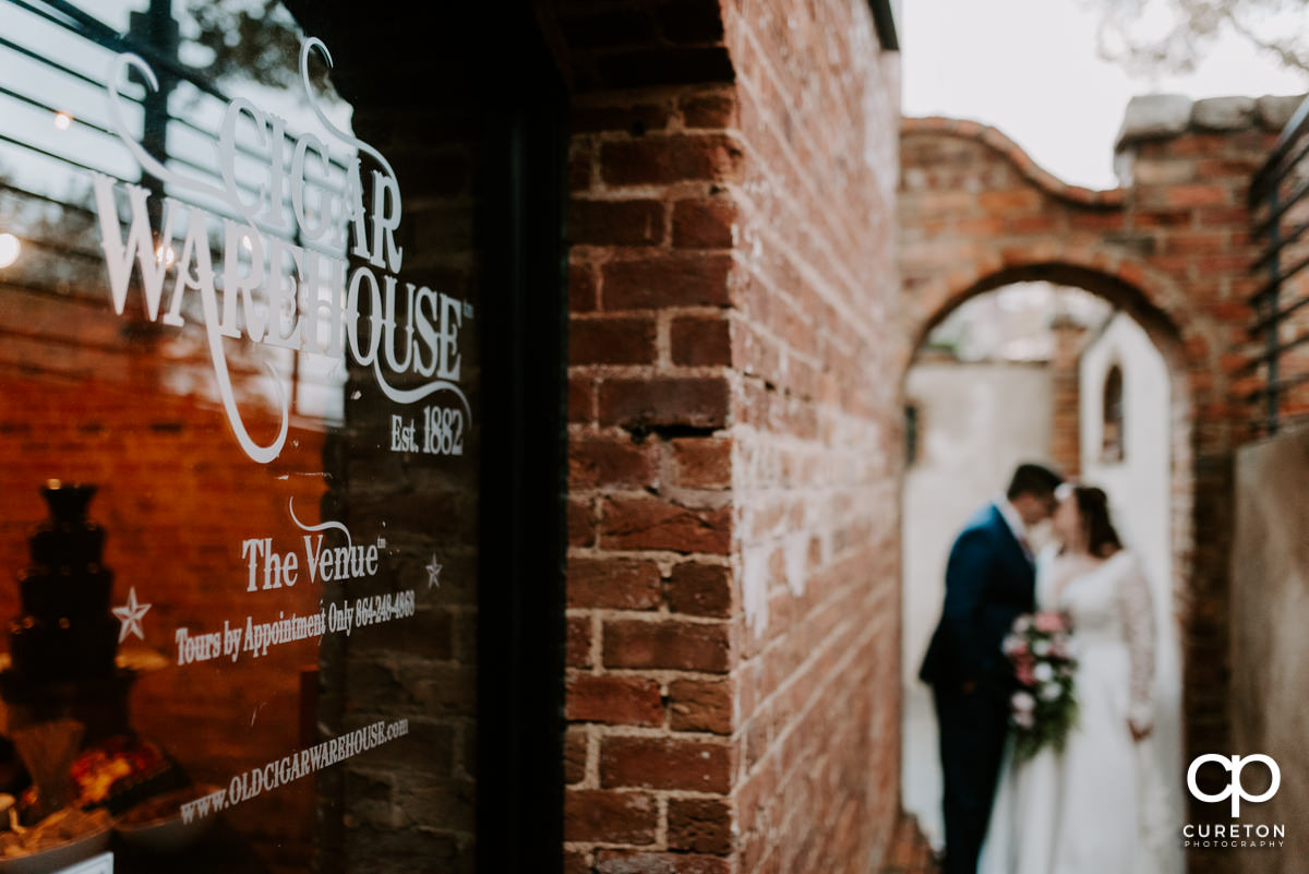 Bride and groom in the background of the Old Cigar Warehouse sign.
