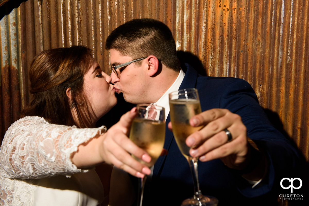Bride and groom toasting champagne flutes.