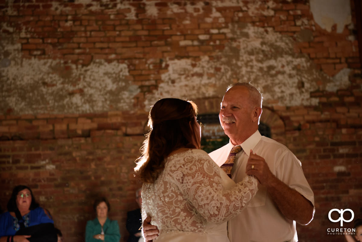 Bride's father smiling while dancing with his daughter.