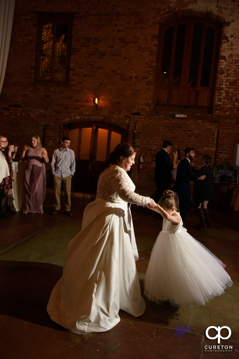 Bride dancing with the flower girl.