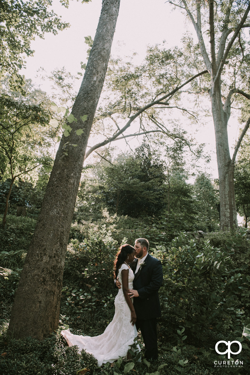 Groom kissing his bride on the forehead in the forest after their wedding ceremony at Falls Park on the Reedy in downtown Greenville,SC.