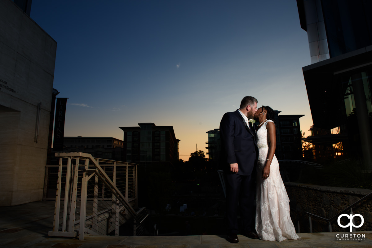 Bride and groom kissing at sunset outside of Larkin's on the River before their wedding reception.