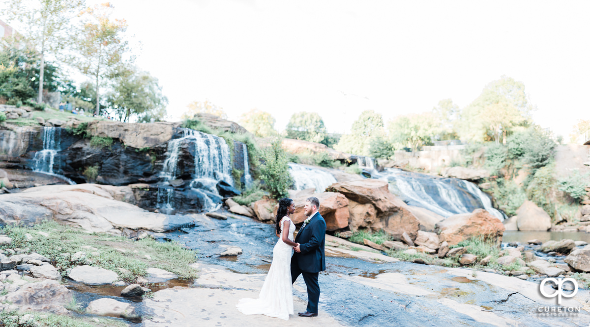 Bride and Groom standing in the waterfall at Falls Park on the Reedy after their wedding ceremony in downtown Greenville,SC.