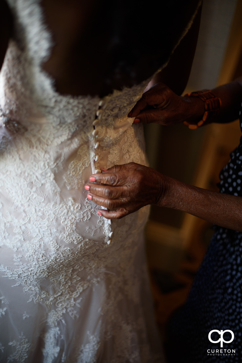 Bride's mother helping her with the dress.