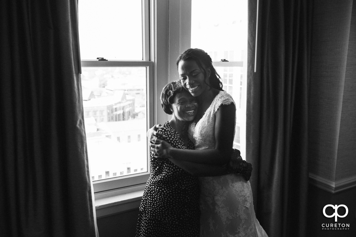 Bride and her mom hugging.
