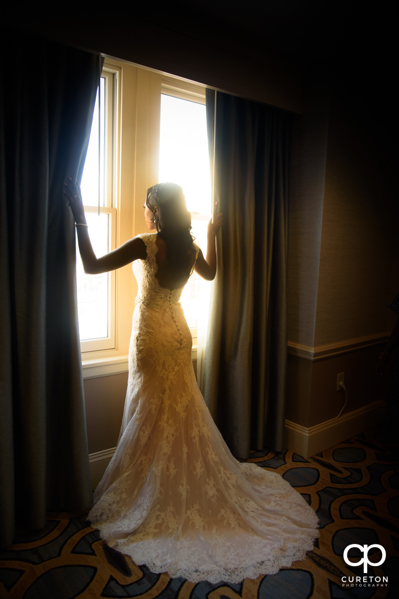 Bride standing in the window light.