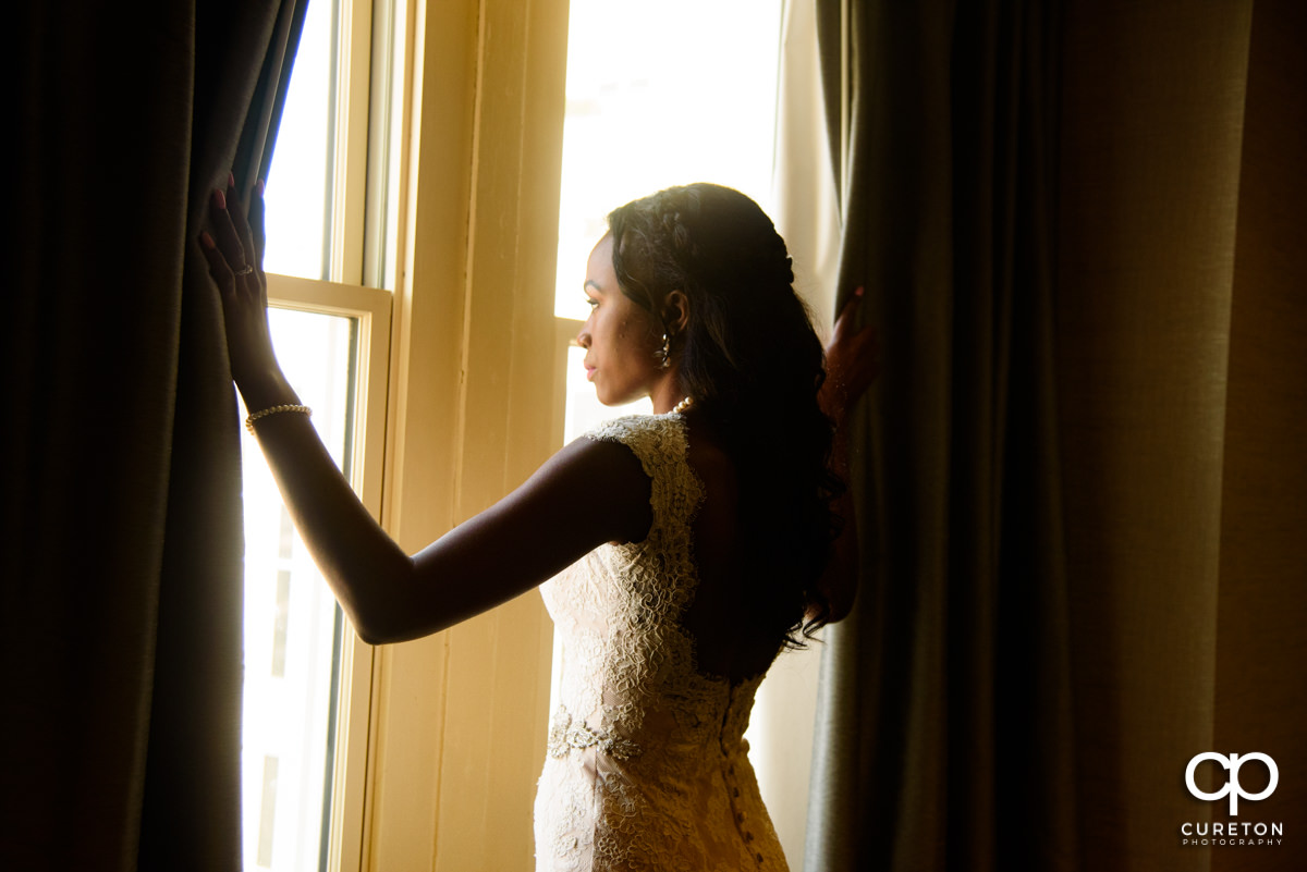 Bride gazing out the window before her wedding.