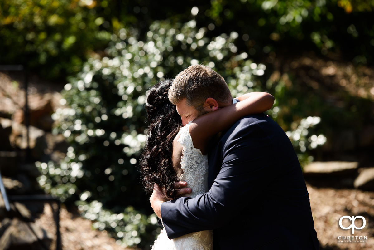 Groom hugging his bride in the park.